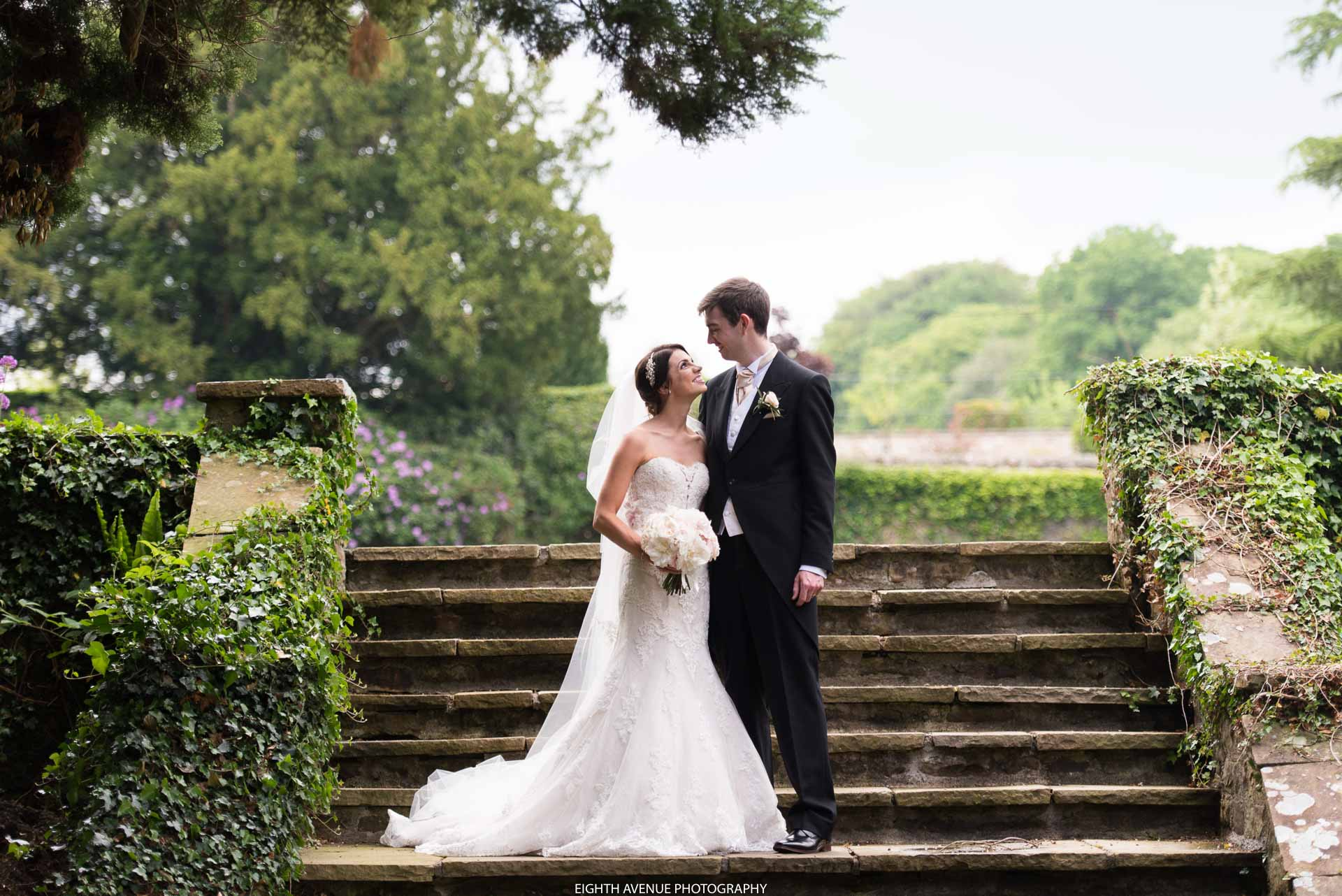 Bride and groom on steps at Eaves Hall