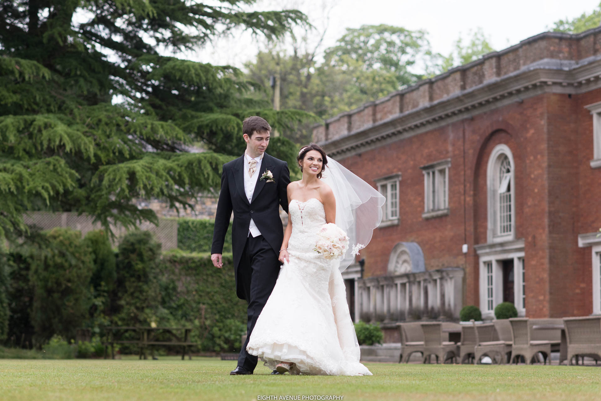 Bride and grooms walking across lawn