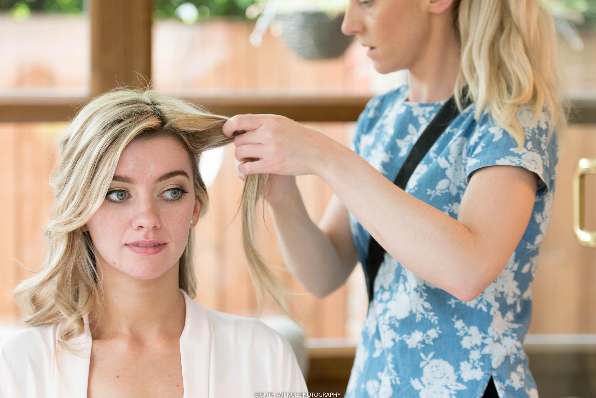 Bridesmaid having hair done for wedding