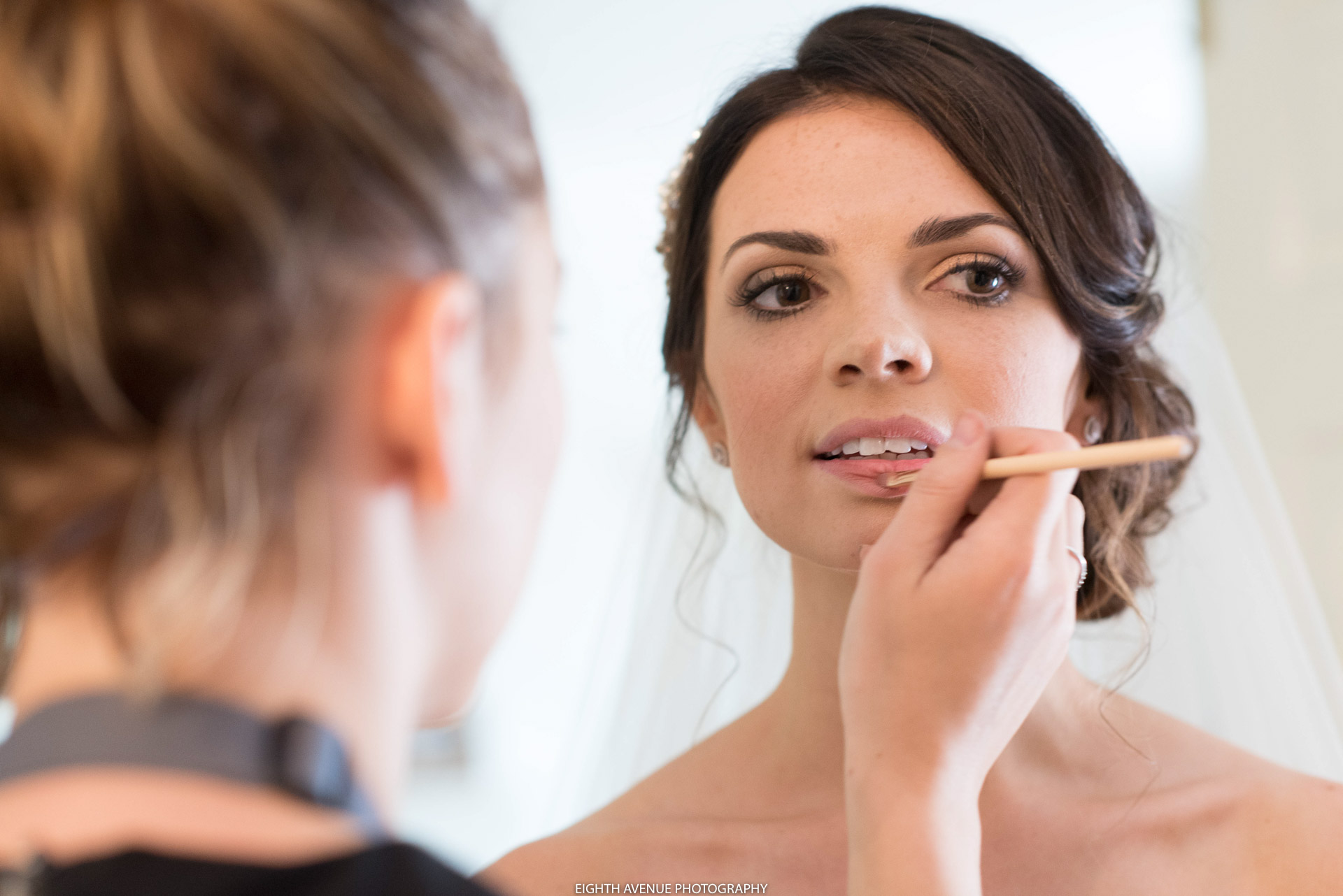 Bride having lip gloss done