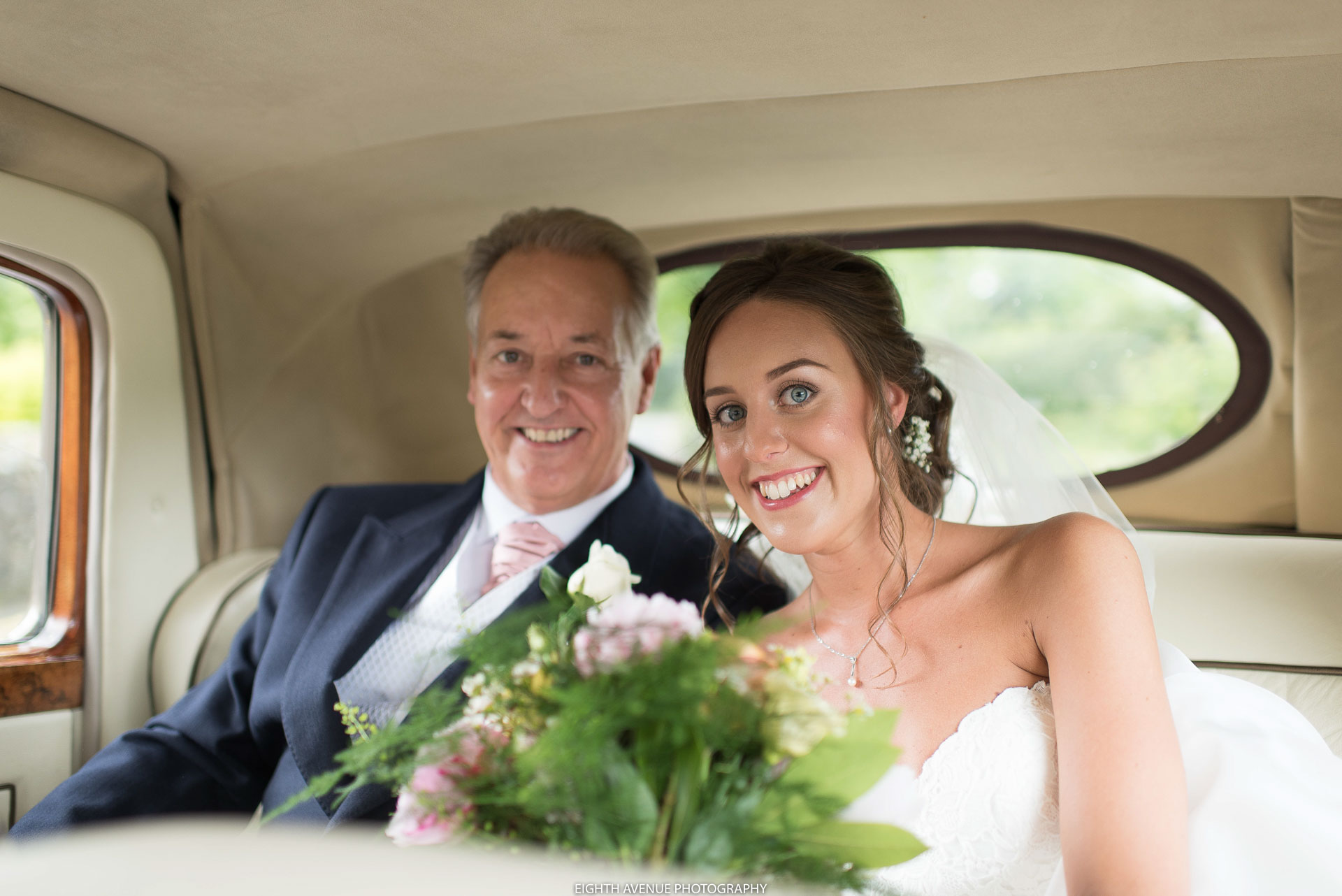 Father of bride and bride in wedding car