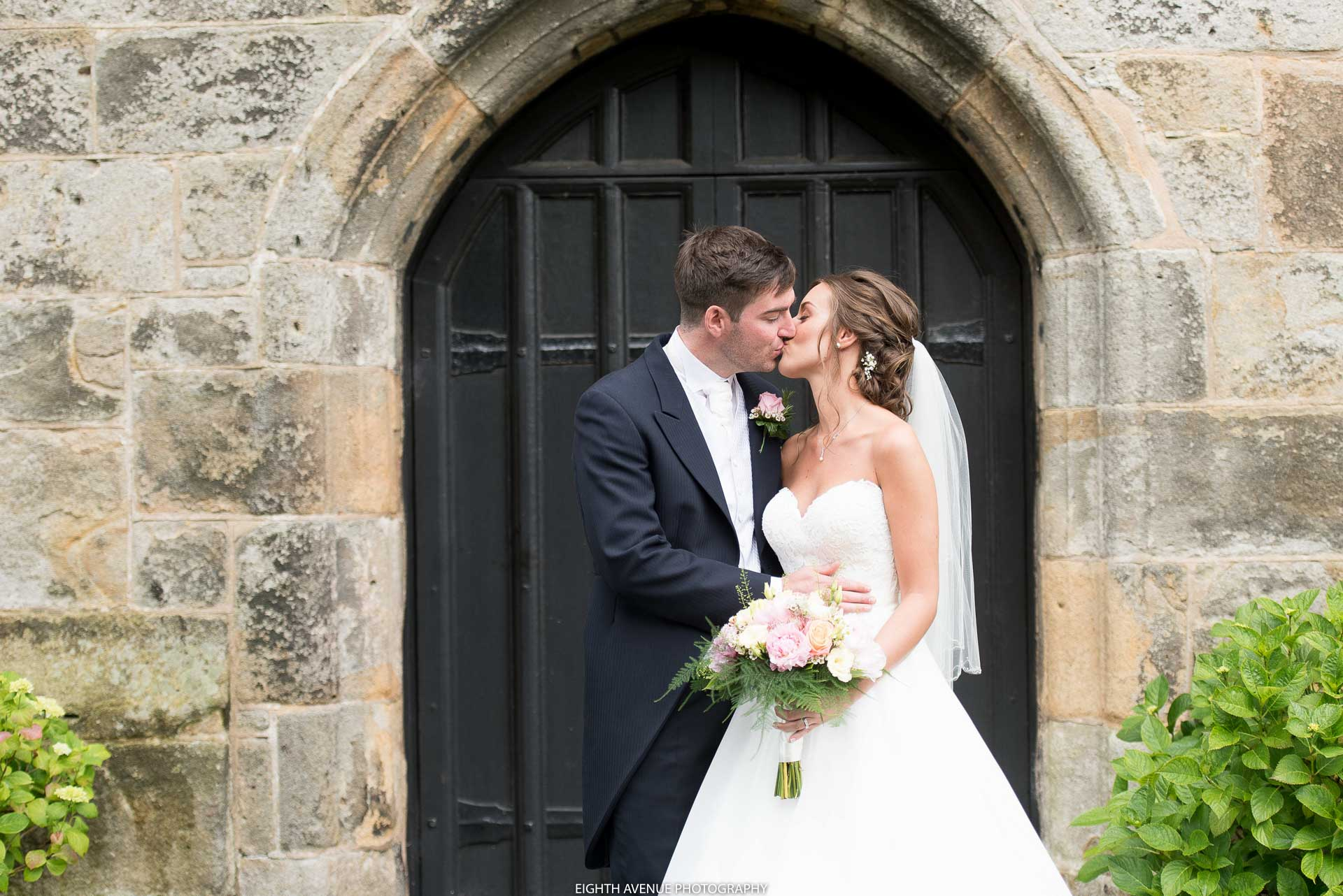Bride and groom kissing outside wedding