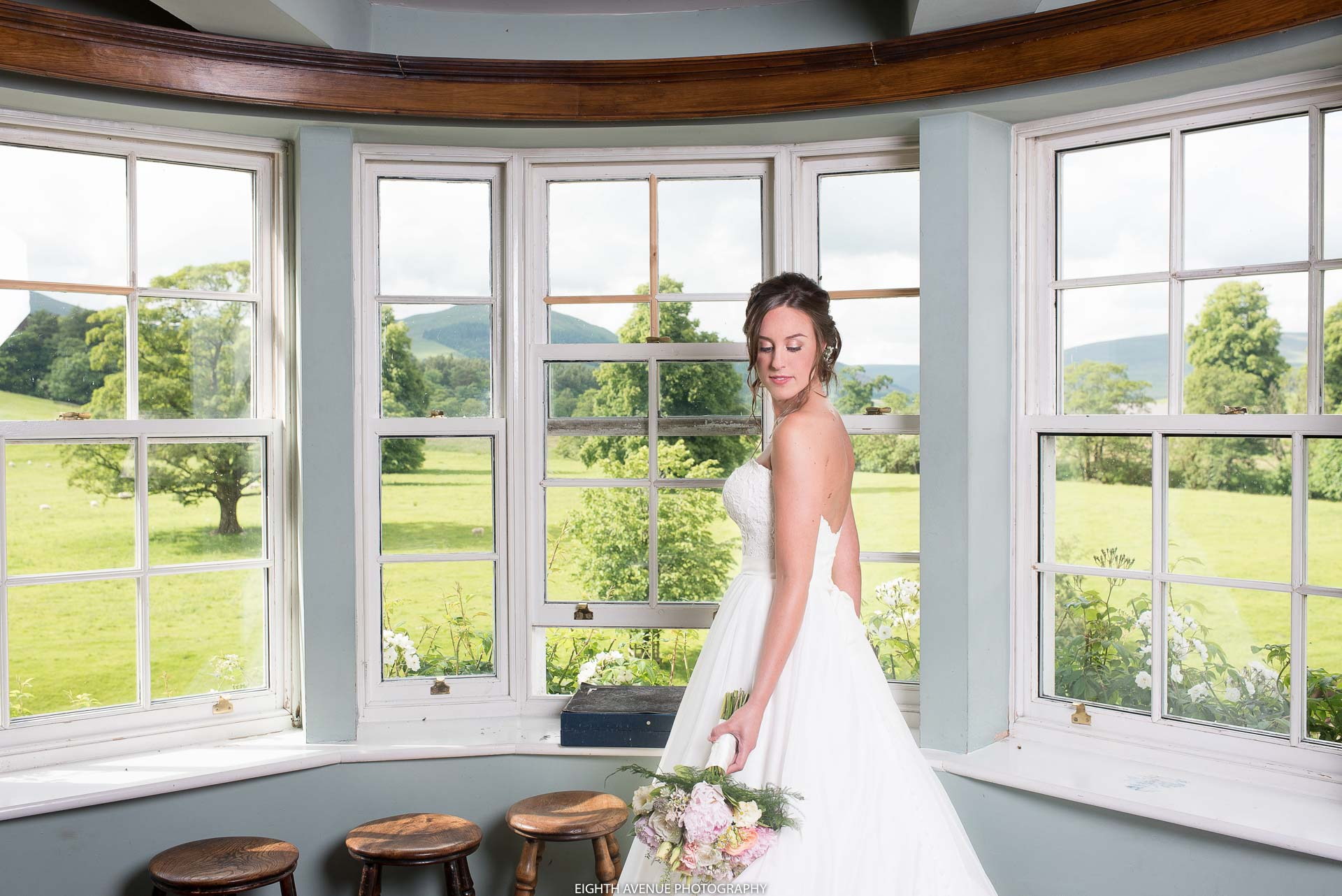 Bride next to window at the Inn at Whitewell
