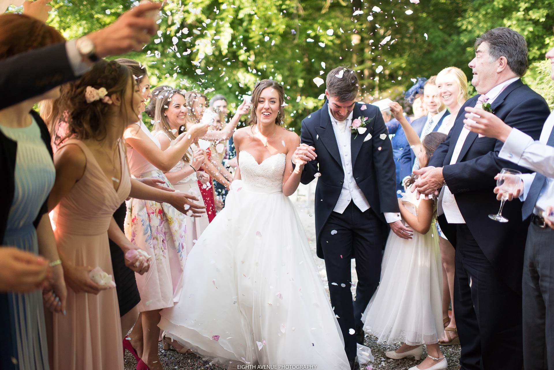 Bride and groom walking through confetti