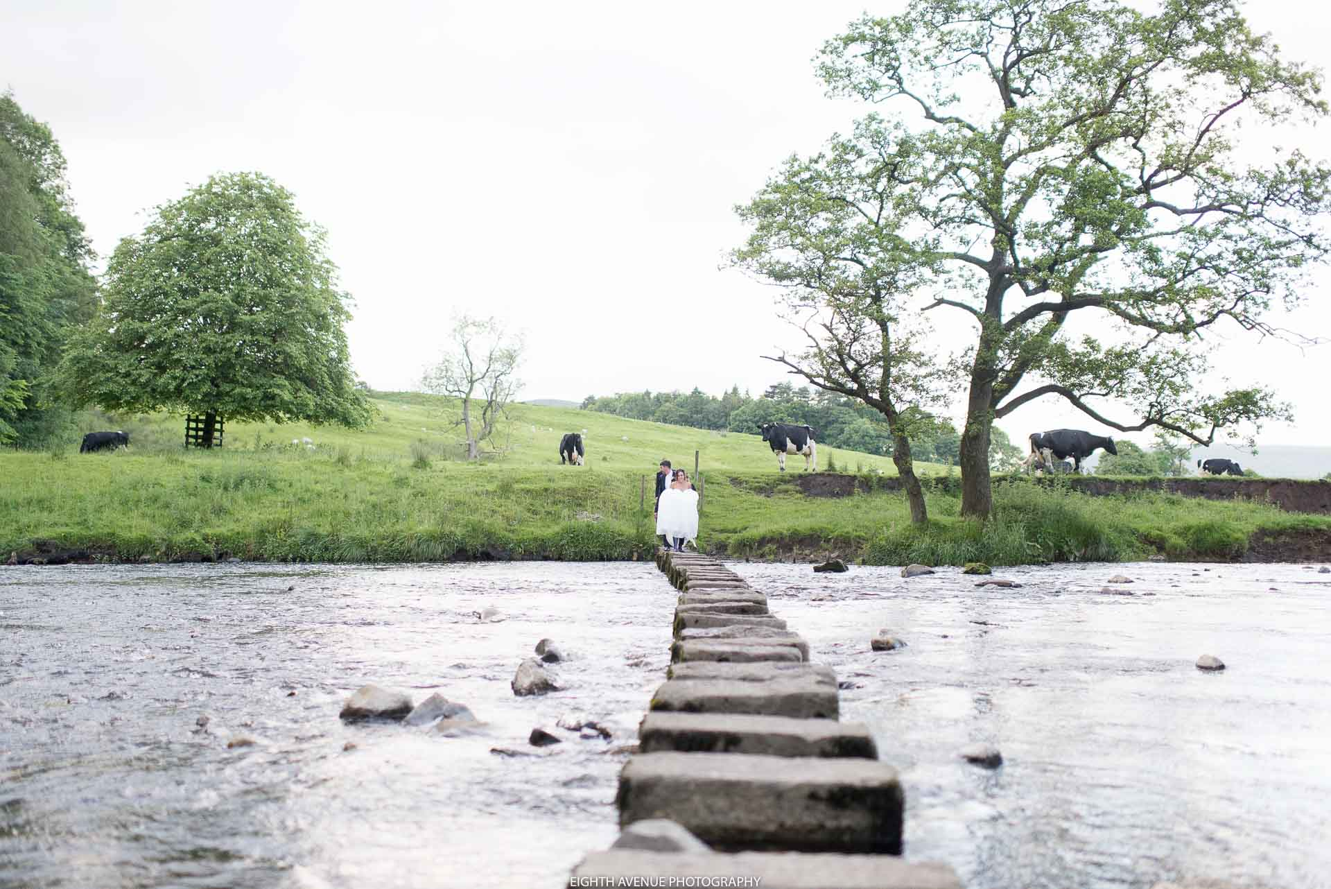 Bride and groom crossing the stepping stones at the Inn at Whitewell