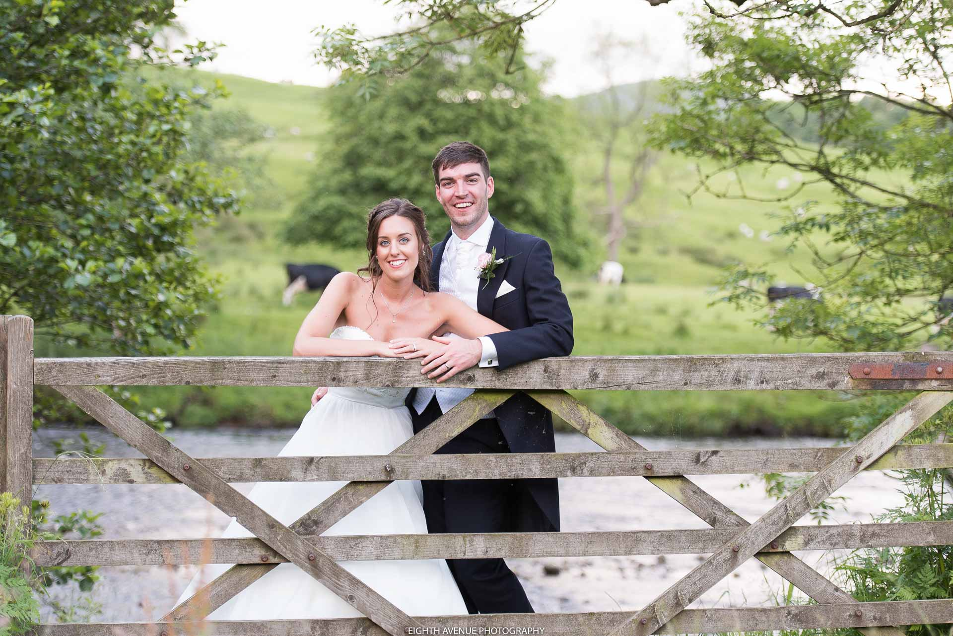 Bride and groom posing by gate at the Inn at Whitewell