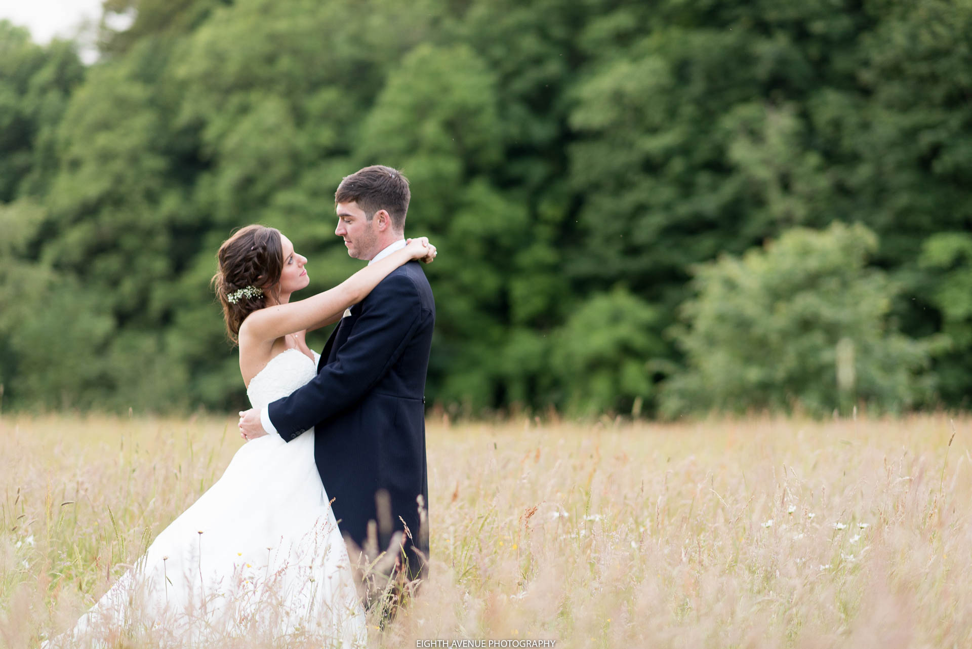 Bride and groom in long grass field