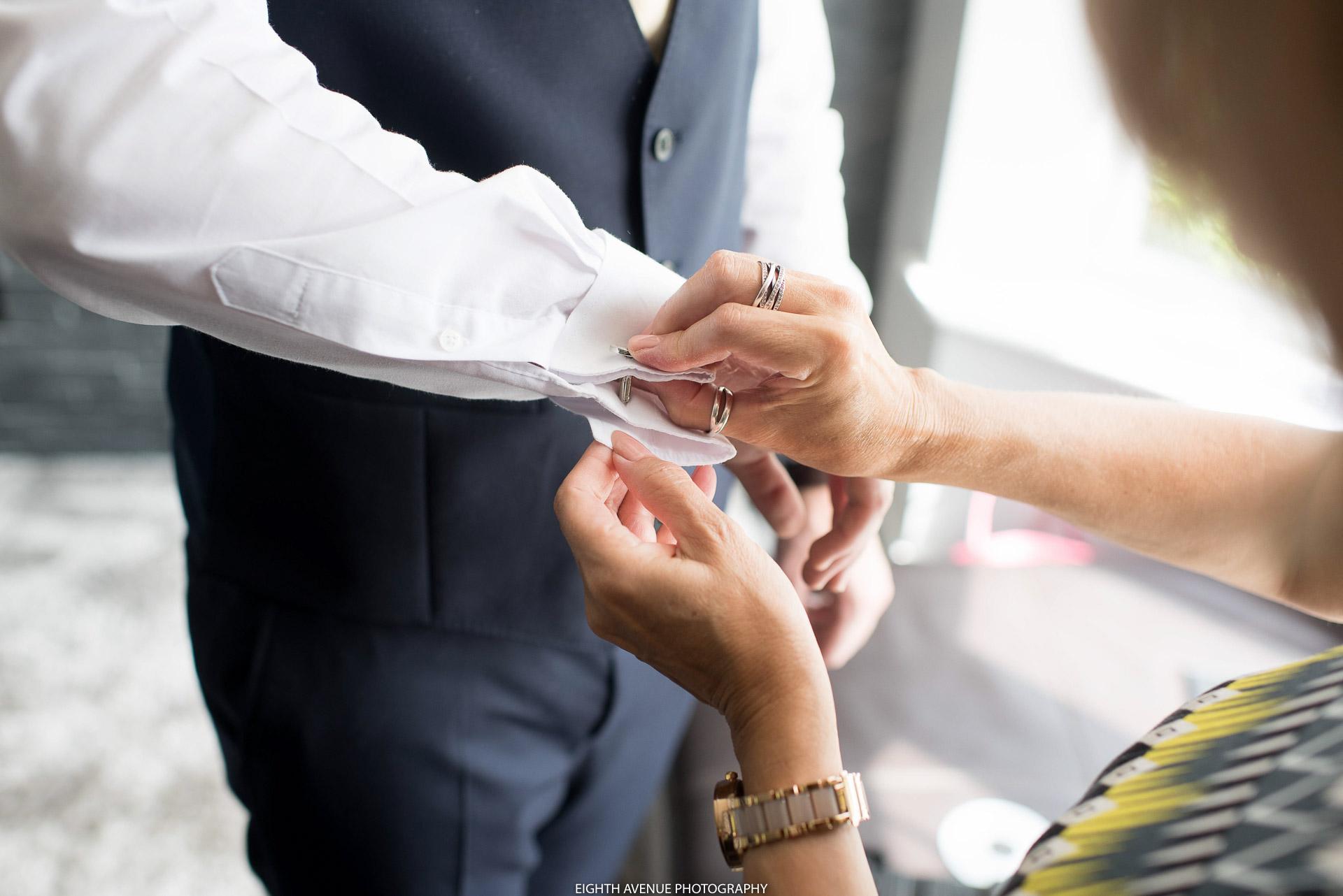 Mother of the groom doing groom's cufflink