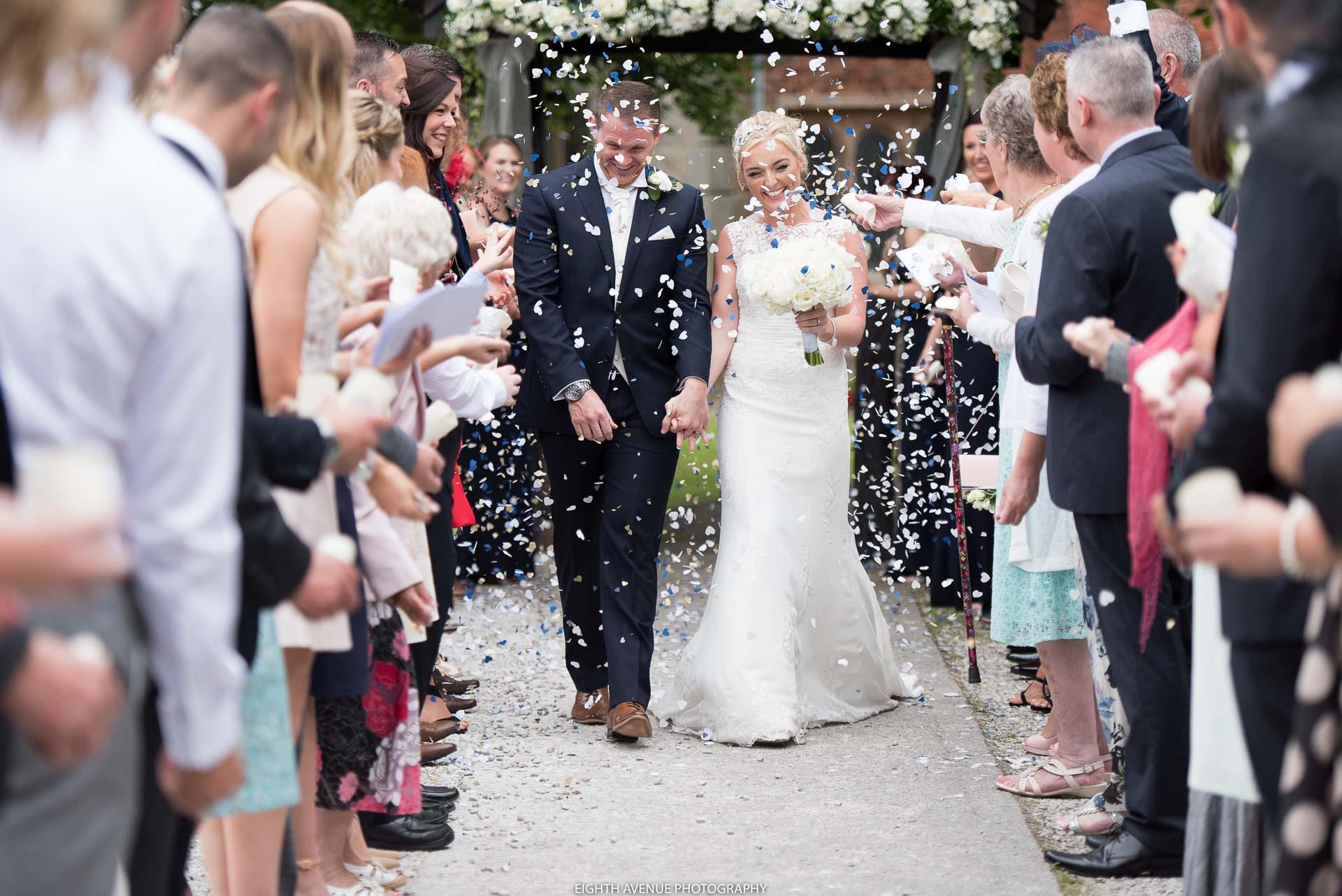Bride and groom walking through confetti outside church