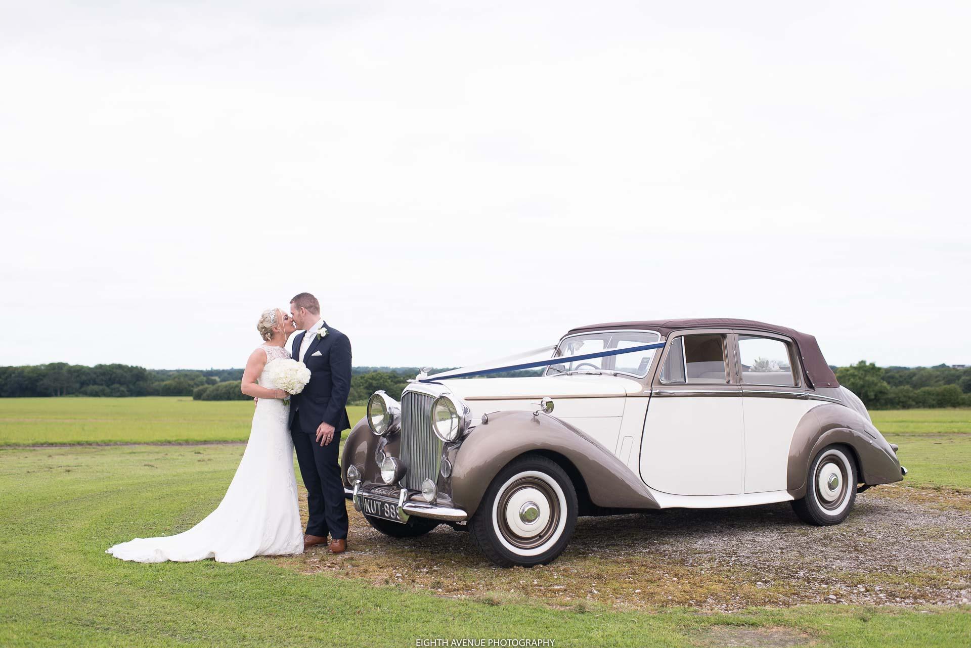 Bride and groom with wedding car at Beeston Manor