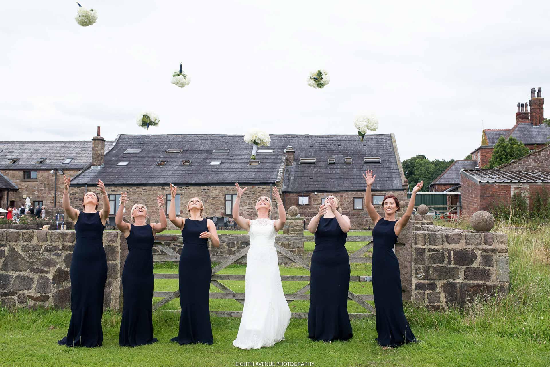 Bride and bidesmaids throwing flowers at Beeston Manor