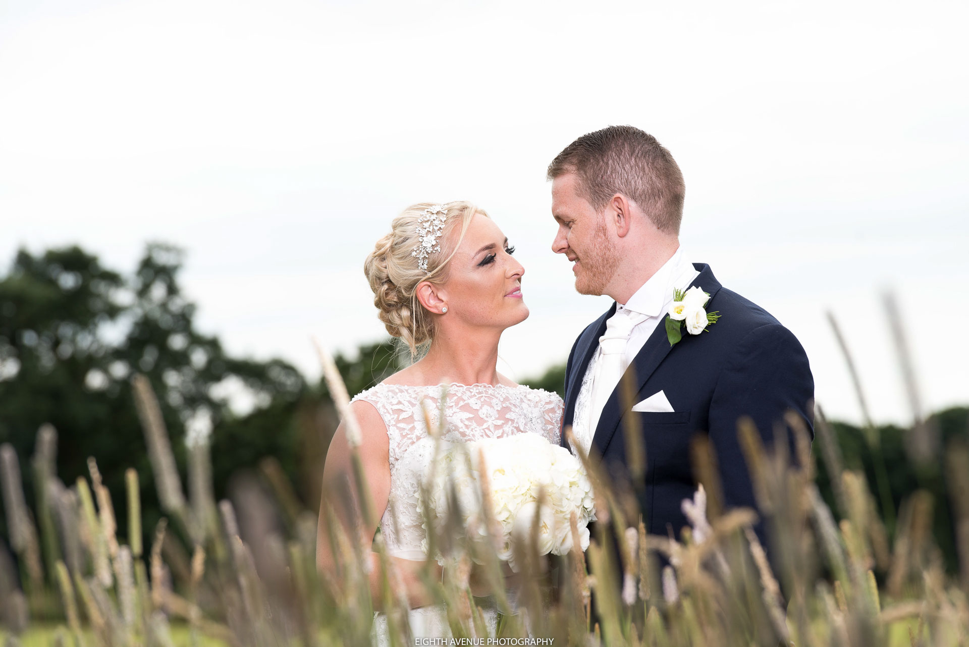 Bride and groom in long grass at their Beeston Manor wedding