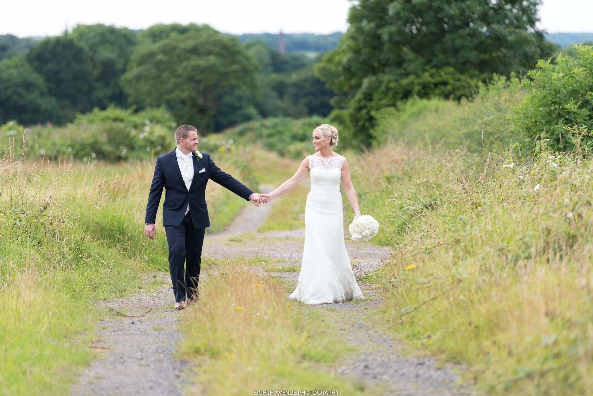 Bride and groom walking down lane at their Beeston Manor wedding