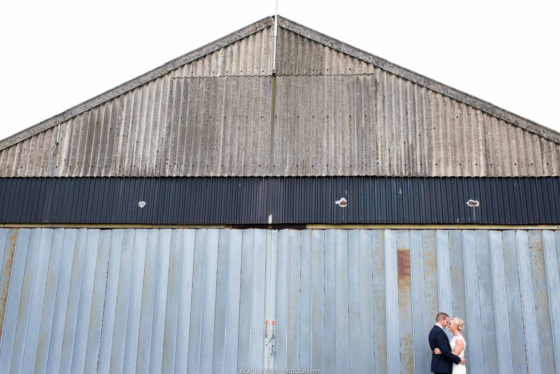 Bride and groom in front of the barn at Beeston Manor