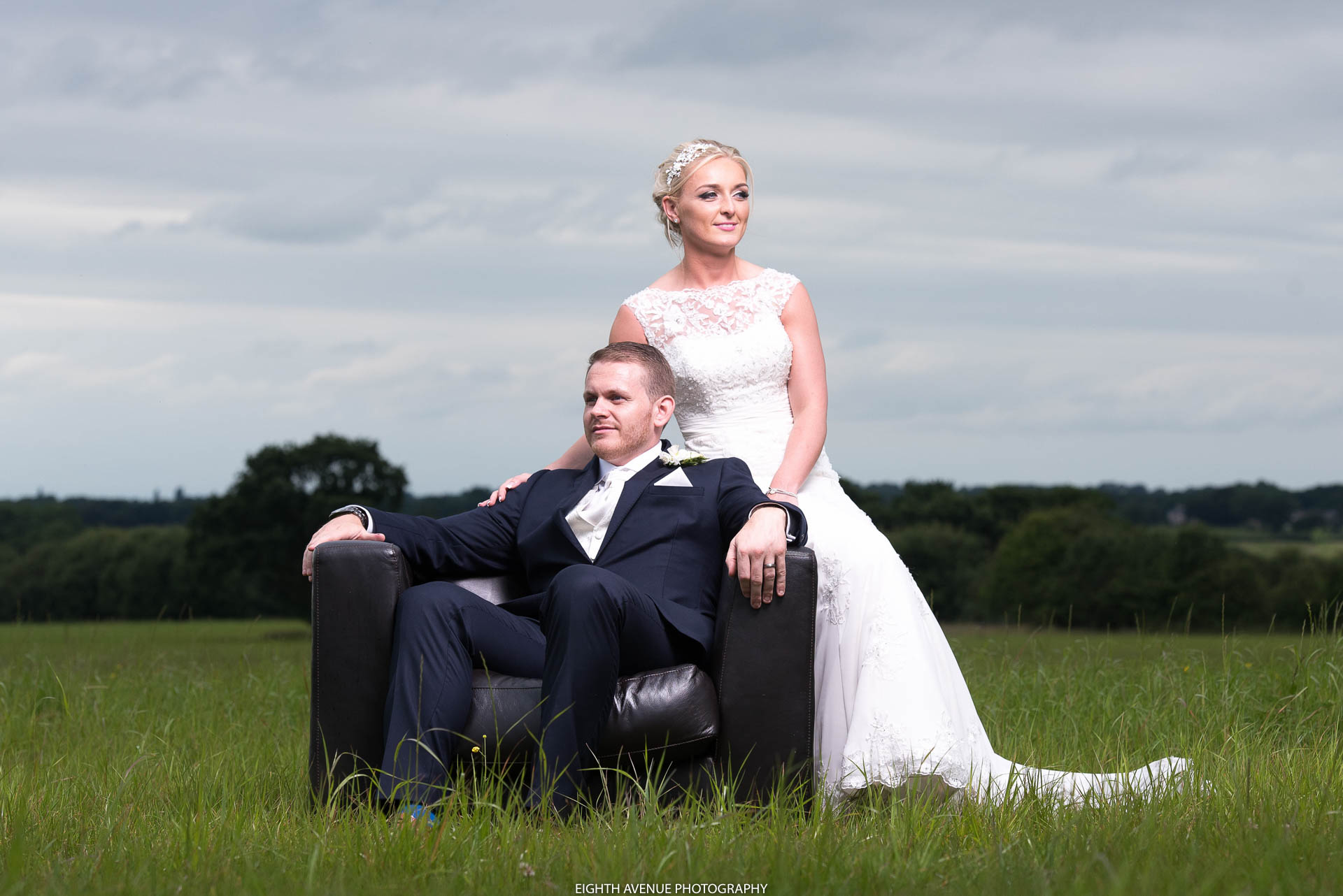 bride and groom on chair in field at Beeston Manor