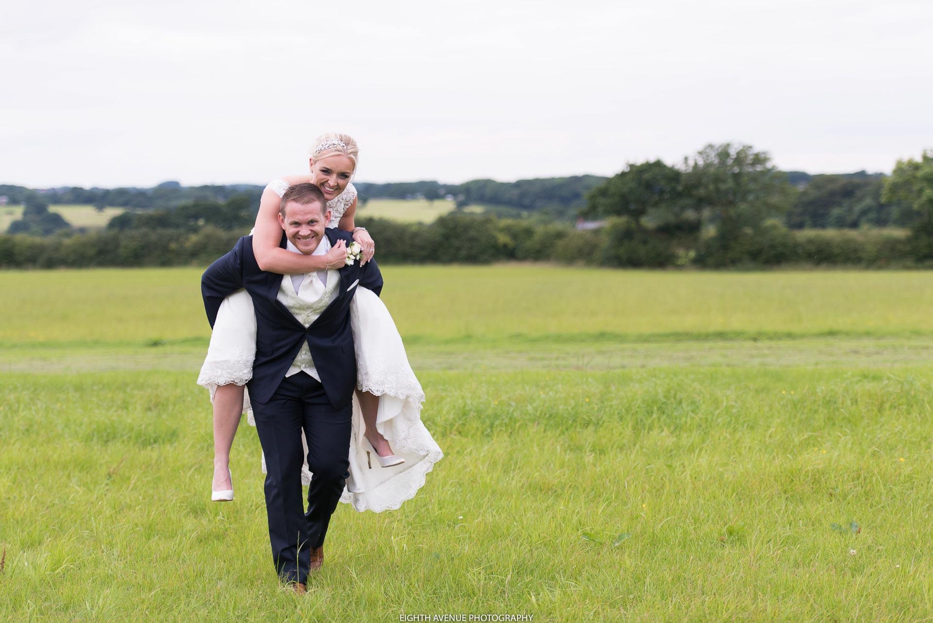 Groom giving bride piggy back at Beeston Manor