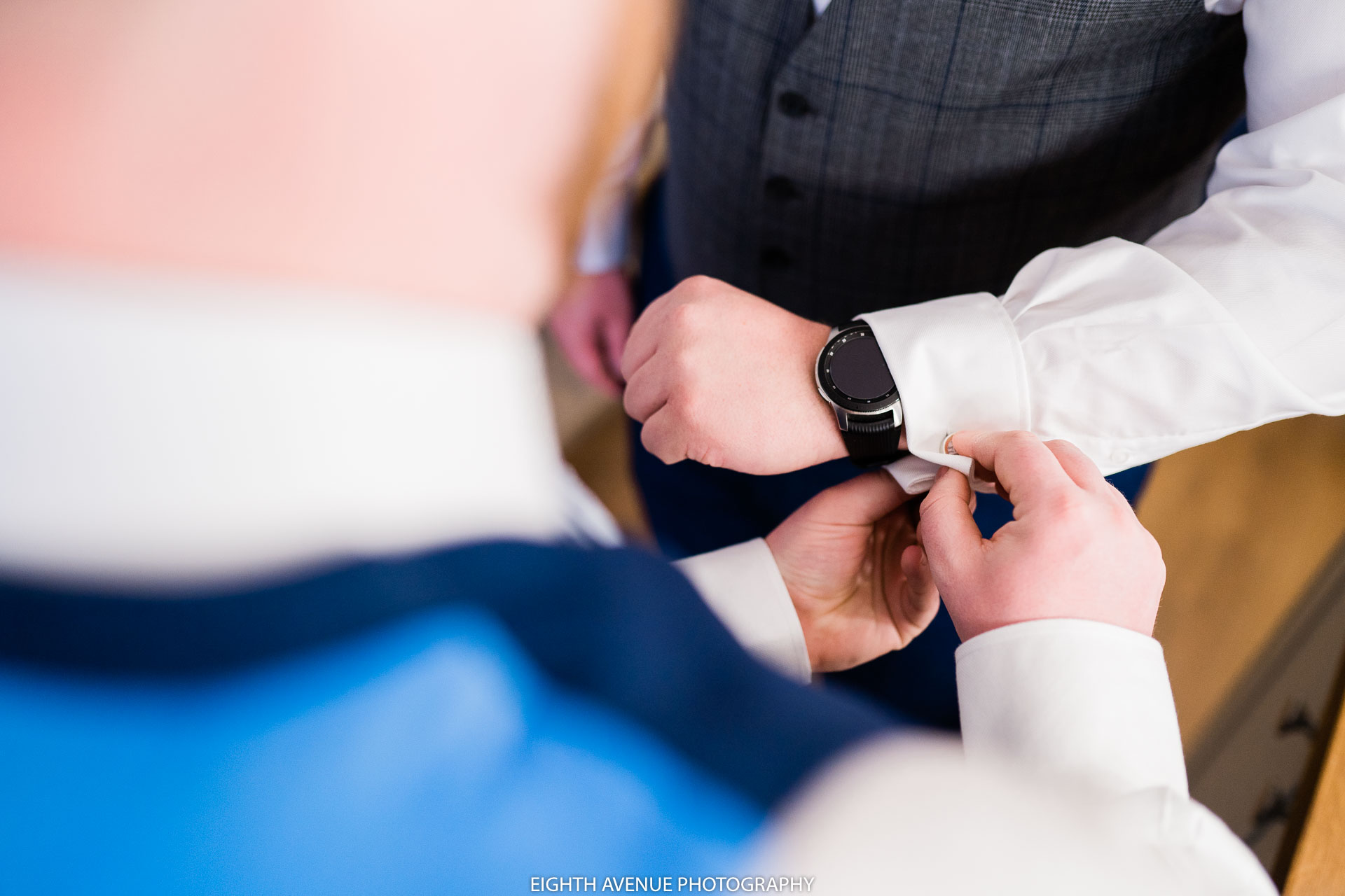 groom putting watch on