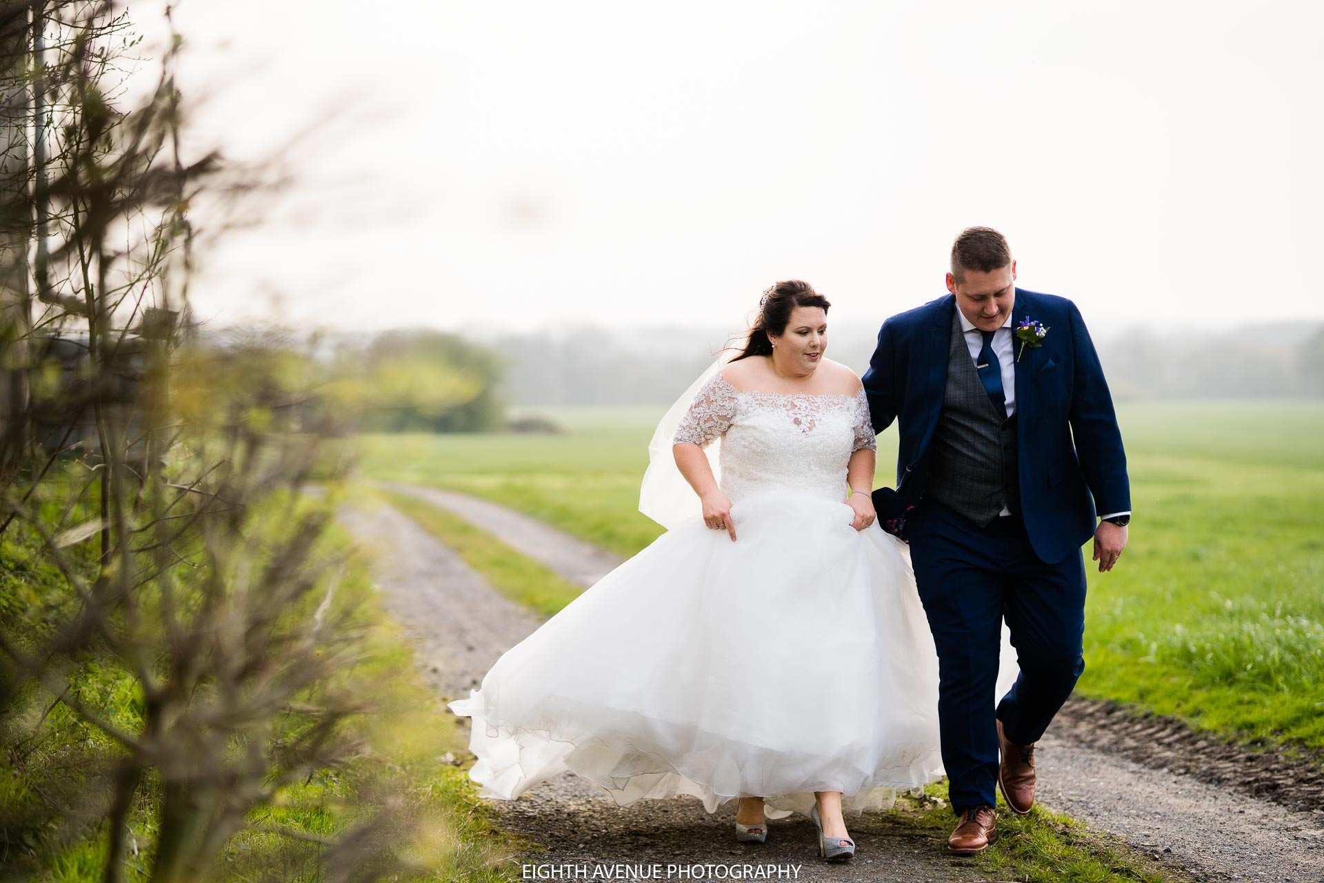 bride and groom walking down country lane