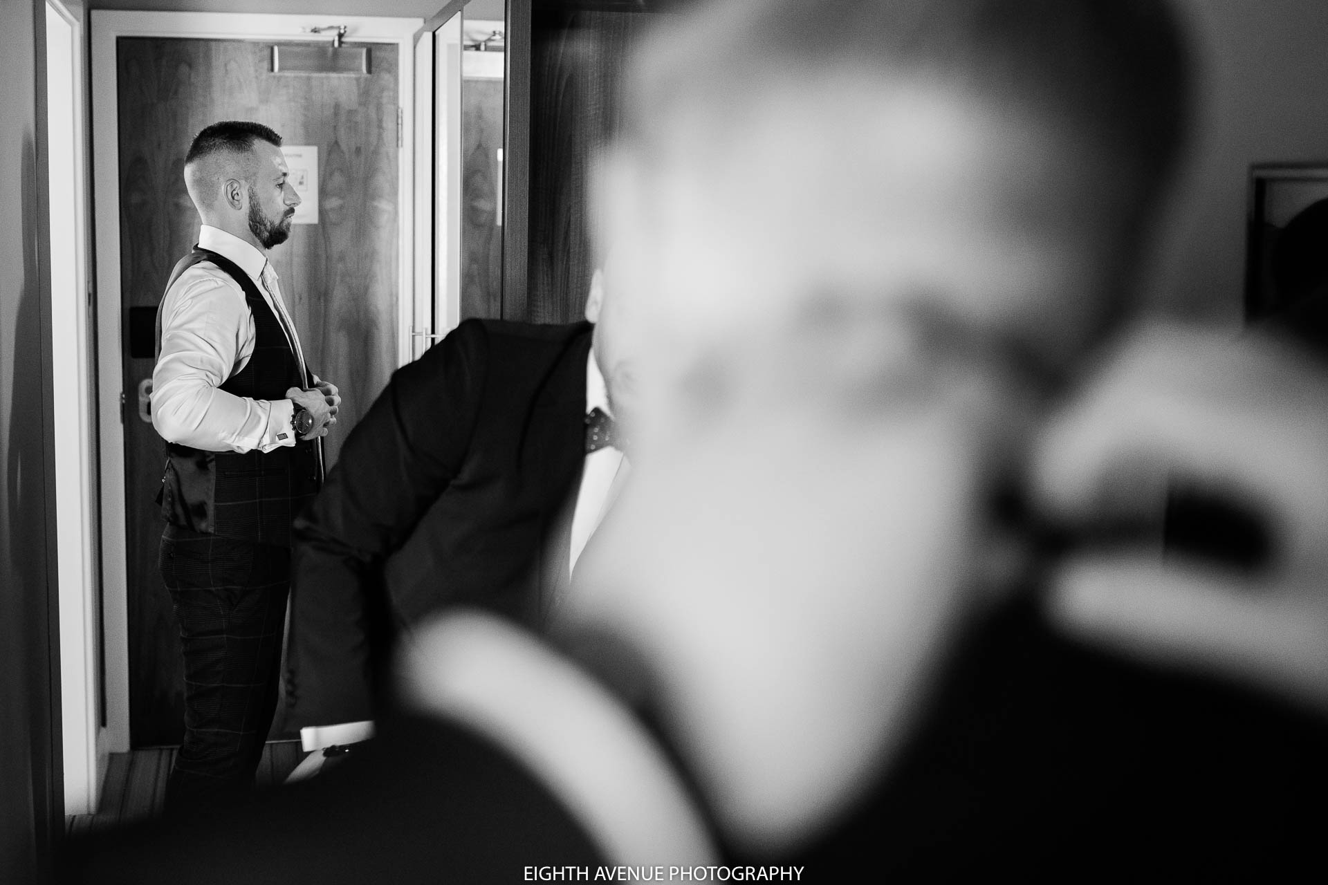 Groom looking in mirror at wedding
