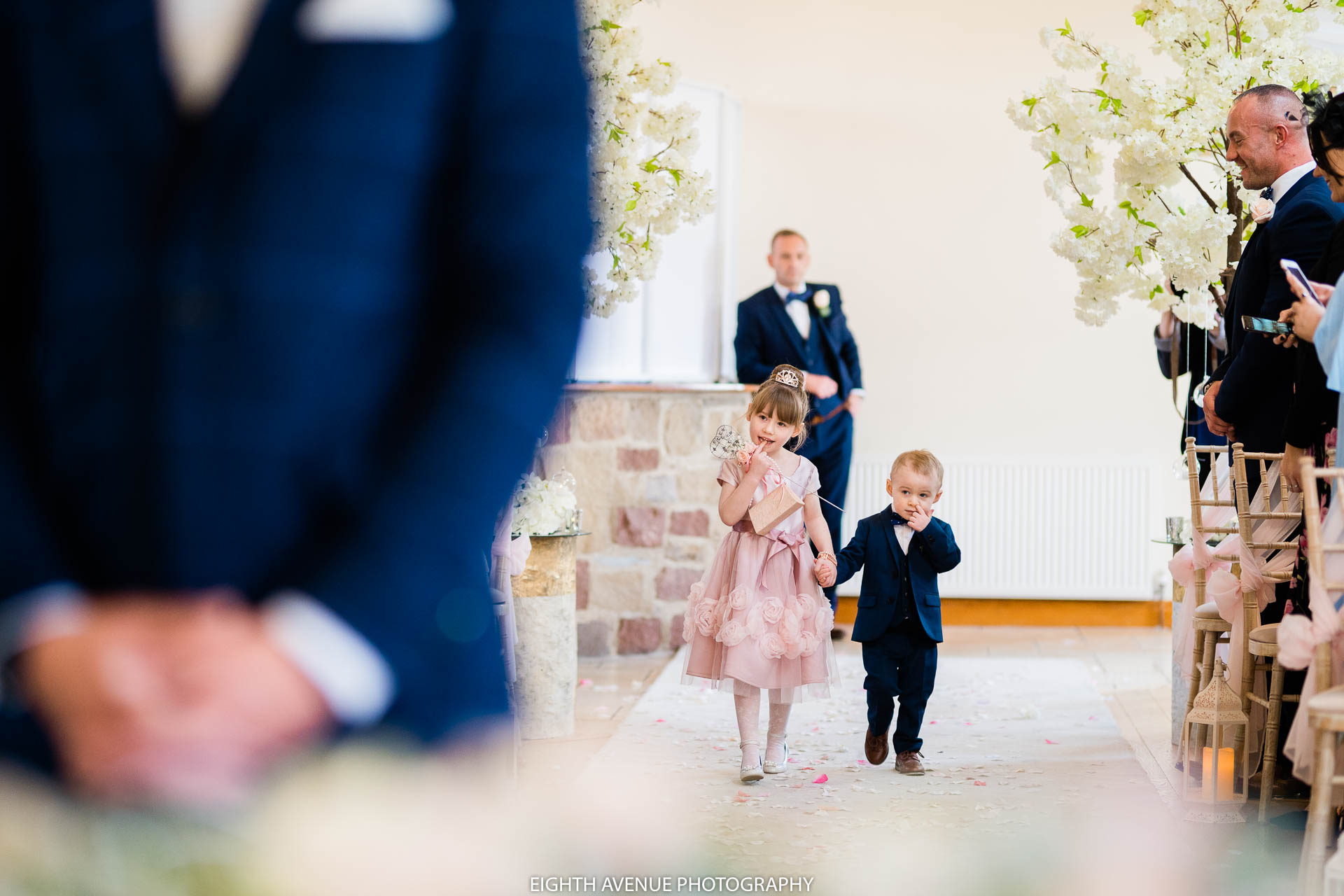 Flower girl and page boy walking down the isle