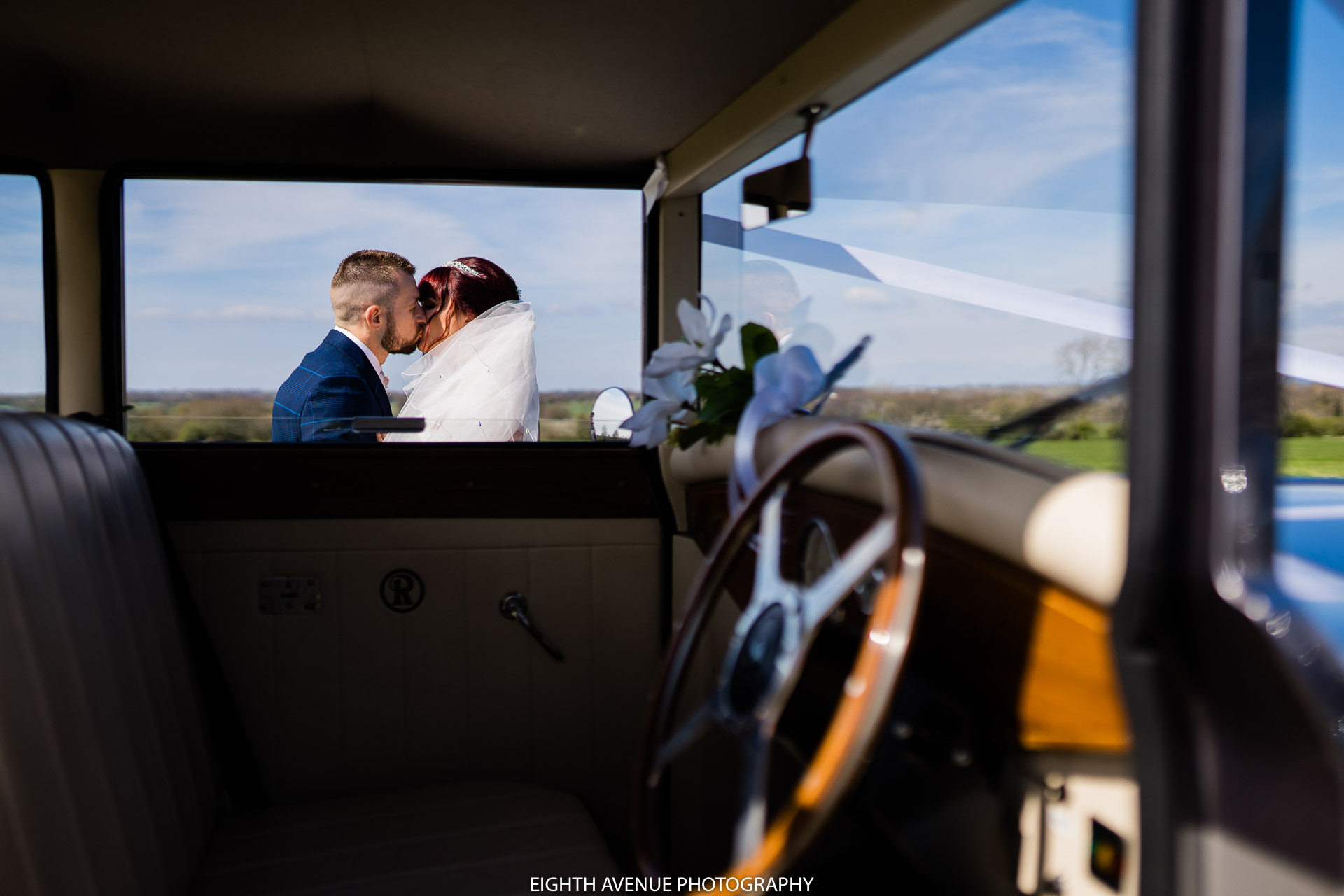 Bride and groom kiss through wedding car