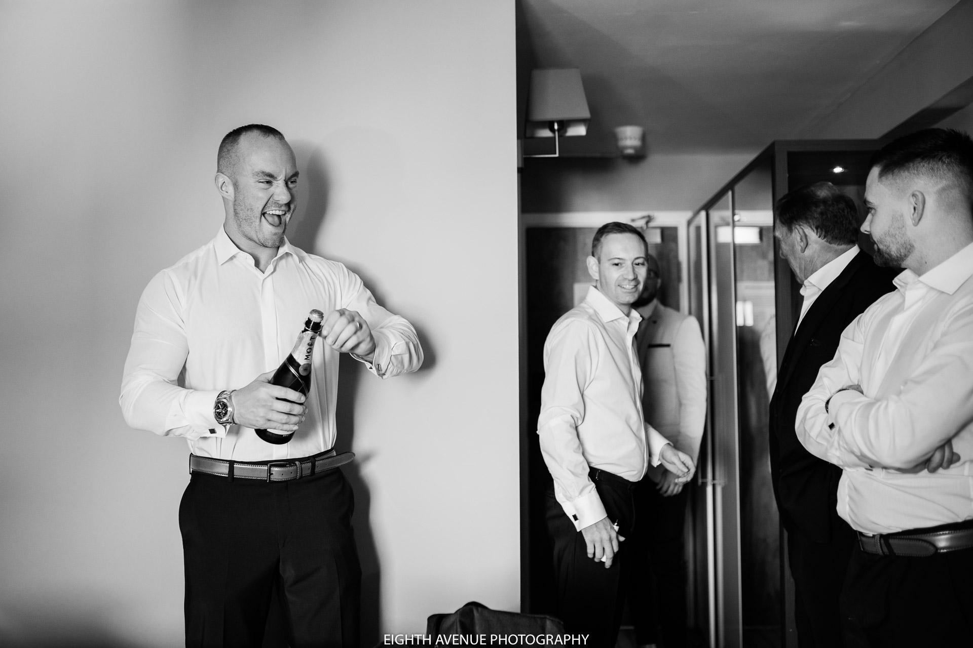 Groomsman opening champagne