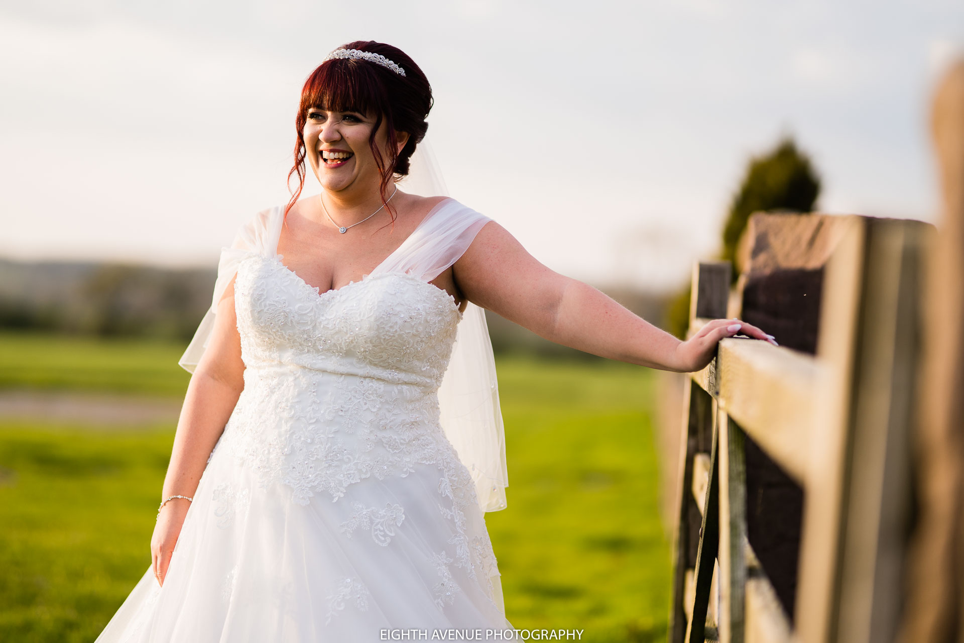 Bride leaning on gate at Beeston Manor
