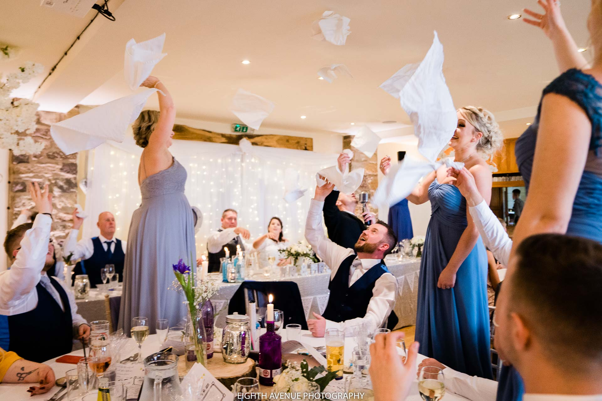 guests throwing knapkins in the air at wedding