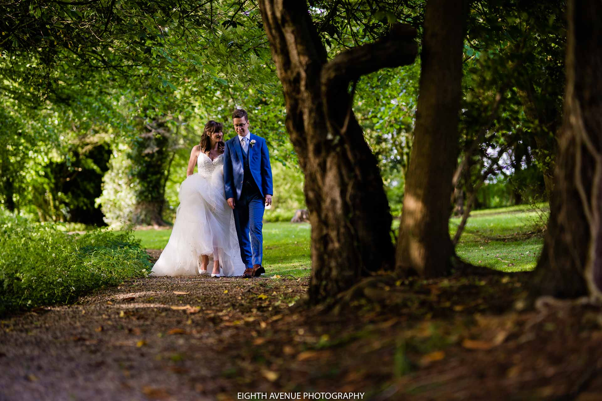 bride and groom waling along path