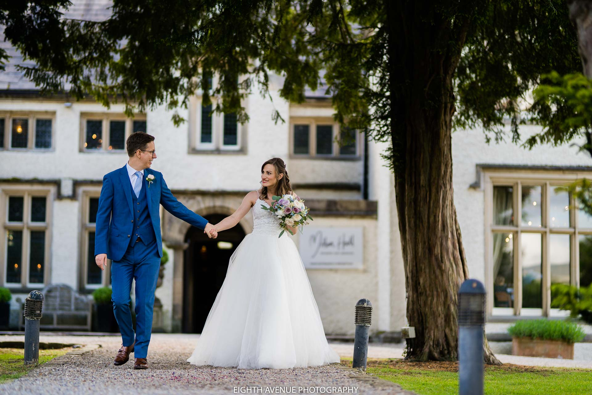 bride and groom in front of Mitton Hall